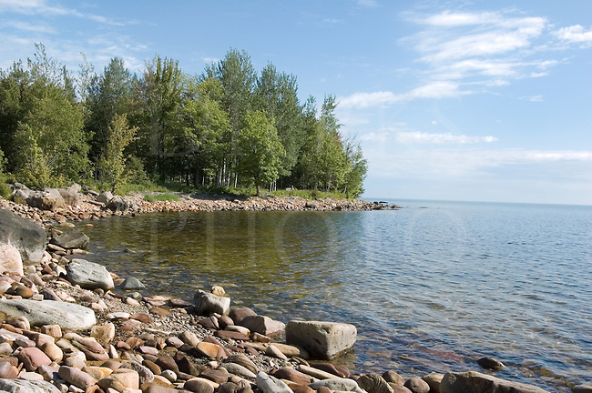 Rocky shore under sunny skies along the waters of Lake Superior, Great Lakes, Michigan.