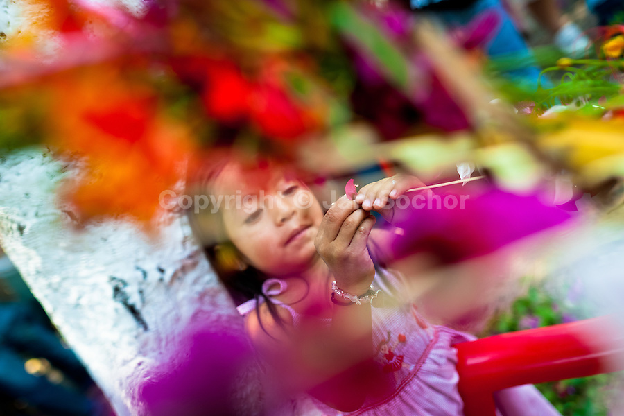 "A Salvadoran girl decorates coconut palm fronds with flower blooms during the Flower & Palm Festival in Panchimalco, El Salvador, 8 May 2011. On the first Sunday of May, the small town of Panchimalco, lying close to San Salvador, celebrates its two patron saints with a spectacular festivity, known as ""Fiesta de las Flores y Palmas"". The origin of this event comes from pre-Columbian Maya culture and used to commemorate the start of the rainy season. Women strip the palm branches and skewer flower blooms on them to create large colorful decoration. In the afternoon procession, lead by a male dance group performing a religious dance-drama inspired by the Spanish Reconquest, large altars adorned with flowers are slowly carried by women, dressed in typical costumes, through the steep streets of the town."