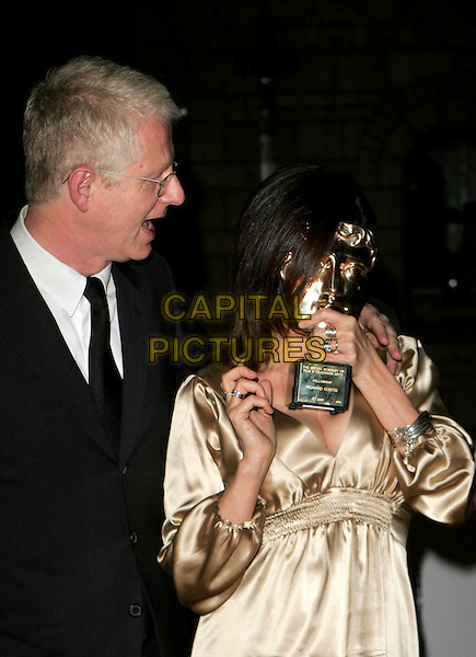 RICHARD CURTIS & EMMA FREUD .The British Academy Television Awards (BAFTA) afterparty at the Natural History Museum, London, England. .May 20th, 2007.half length black suit jacket beige gold dress satin hiding covering face funny profile glasses trophy award.CAP/AH.©Adam Houghton/Capital Pictures