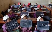 Bangladeshi students display their handwritings on their blackboards to their teacher at an Islamic education school on the outskirts of Dhaka, Bangladesh.
