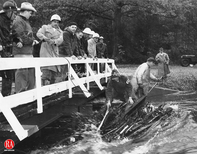 Winsted Civil Defense volunteers and firemen battled to save this bridge over a tributary of the Still River near the municipal sewage disposal plant on October 15, 1955. Debris had become lodged against the center pier of the structure erected temporarily after the August 19th flood. The pressure of the water was so great that the two men standing on the debris in the stream were not able to budge it until a winch from an Army vehicle was hooked into it with the cable the men on the span are holding.