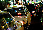 Taxis line up to pick up passengers outside a railway station in Tokyo, Japan. Photographer: Robert Gilhooly.
