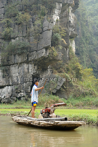 Asia, Vietnam, Tam Coc near Ninh Binh. In the watery landscape of Tam Coc (Three Caves) young vietnamese man working from his boat.