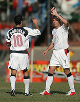 09 February, 2005. Eddie Lewis (7) and Landon Donovan (10) celebrate a US goal during the World Cup qualifier at Queen's Park Oval in Port of Spain, Trinidad and Tobago.  The USMNT defended Trinidad and Tobago 2-1.
