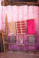 A row of chairs which have seen better days against a pink-painted partition wall in the market