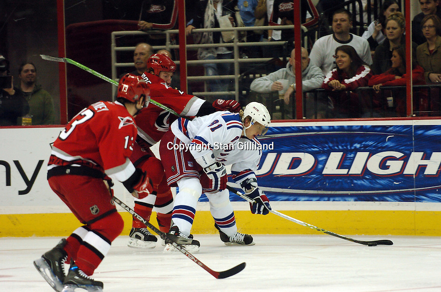 Carolina Hurricanes' defenseman Mike Commodore keeps a hand on the New York Rangers' Marcel Hossa, right, of Slovakia during their game Tuesday, March 14, 2006 at the RBC Center in Raleigh, NC. Carolina won 5-3.