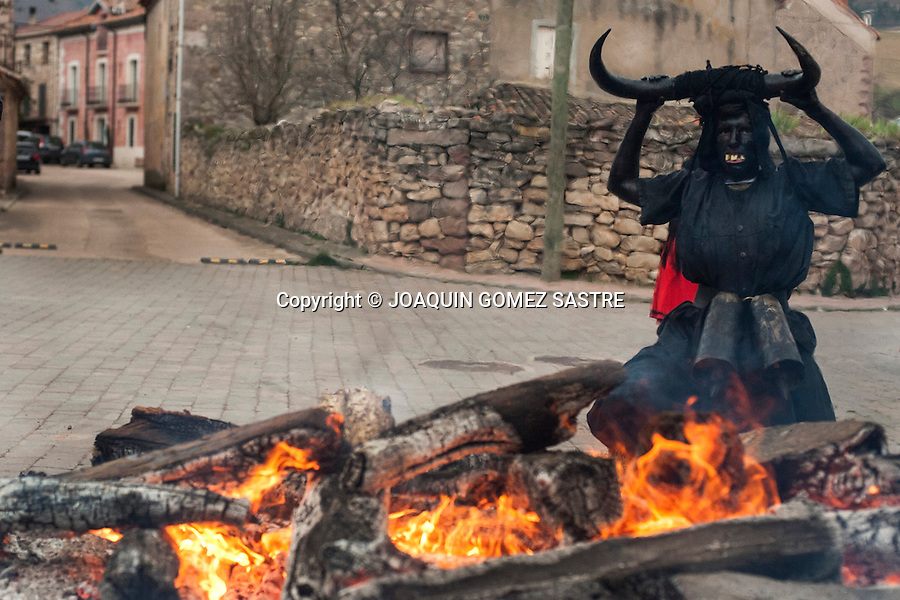 One participant with his devil costume at the carnival of Luzon (Guadalajara) poses in front of a fire
