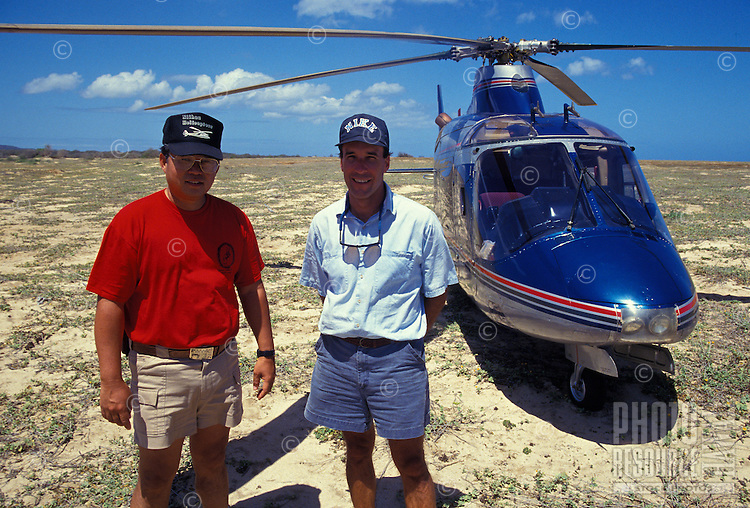 Helicopter pilots David Nekomoto (left) and George Stever touching down on the Island of Niihau after ferrying passengers from Kauai, with helicopter in the background