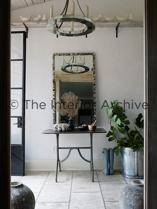 A nine-foot tall steel door replaced the original wooden one in the entrance hall which has a reclaimed French limestone floor