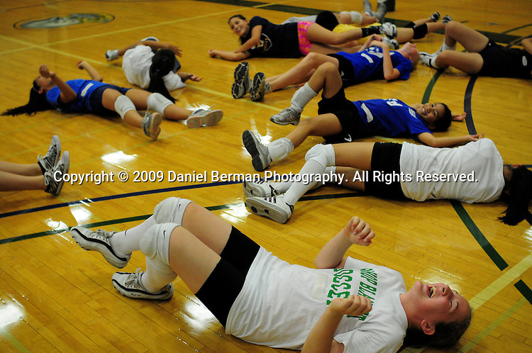 Daniel Berman/Special to The Enterprise..Alexandra Pinkley, bottom-right, wiggles on the floor during a warm-up exercise as part of a youth volleyball camp held Monday July 27 at Shoreline Community College...Shoreline, WA