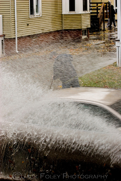 Man cleaning a storm drain during a flash flood getting splashed by a passing vehicle.