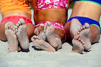 Sandy feet of girlfriends at the beach.