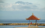 A family rests on the beach in Nusa Dua, Indonesia with the shadow of Gunung Agung in the distance