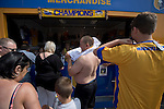 Mansfield Town supporters trying on their team's new strips at a kiosk outside Field Mill stadium during an open day held for the club's supporters. Mansfield Town achieved promotion back to England's Football League by winning the Conference National in season 2012-13. Field Mill was the oldest ground in the Football League, hosting football since 1861 although some reports date it back as far as 1850, with Mansfield Town having played there since 1919.