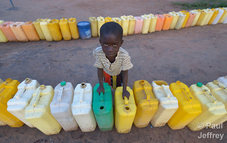 A boy keeps watch on a row of jerry cans before dawn in the Rhino Refugee Camp in northern Uganda. As of April 2017, the camp held almost 87,000 refugees from South Sudan, and more people were arriving daily. About 1.8 million people have fled South Sudan since civil war broke out there at the end of 2013. About 900,000 have sought refuge in Uganda. <br /> <br /> Because water pumps in the camp are solar-powered, water can only be obtained during daylight hours. Refugees will therefore line up their jerry cans overnight in order to be among the first to get water in the morning.<br /> <br /> The Global Health Program of the United Methodist Church has supported work to improve access to safe drinking water in the camp.