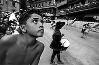 © Francesco Cito / Panos Pictures..Siena, Tuscany, Italy. The Palio. ..A boy watches the historical parade which takes place before the race...Twice each summer, the Piazza del Campo in the medieval Tuscan town of Siena is transformed into a dirt racetrack for Il Palio, the most passionately contested horse race in the world. The race, which lasts just 90 seconds, has become intrinsic to the town's heritage since it was first run in 1597..