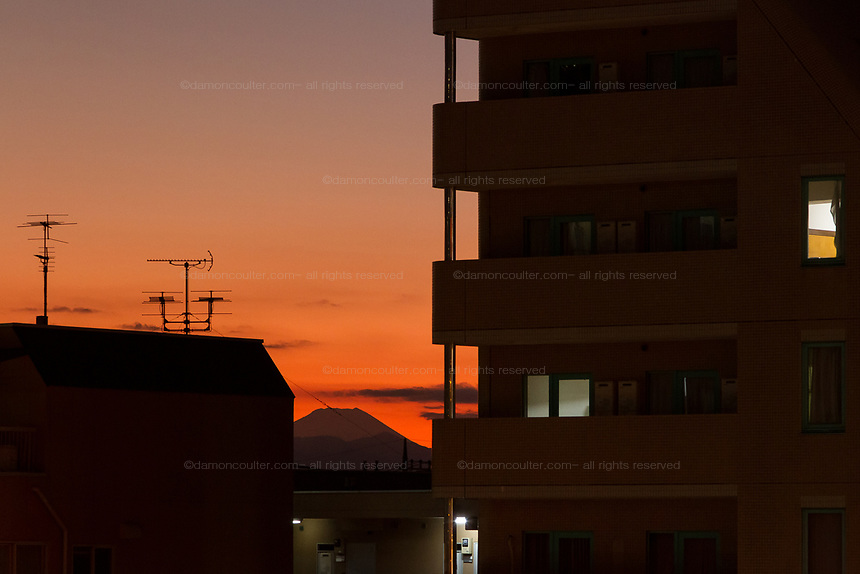 Mount Fuji at sunset seen between apartment buildings in Yoga, Tokyo, Japan. Sunday December 8th 2019