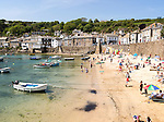 People on crowded beach in Mousehole  village, Cornwall, England, UK