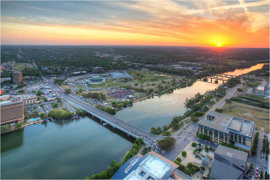 From the tallest point in the Austin Skyline, the balcony from the 54th floor penthouse of the Austonian offers spectacular views of Ladybird Lake, 1st Street Bridge, Lamar Bridge, Zilker Park, and the distant Texas Hill Country looking southwest. ..This image was taken at sunset. A music festival is in full swing at Auditorium Shores in front of the Long Center. It is a good Saturday night to be in Austin, Texas.