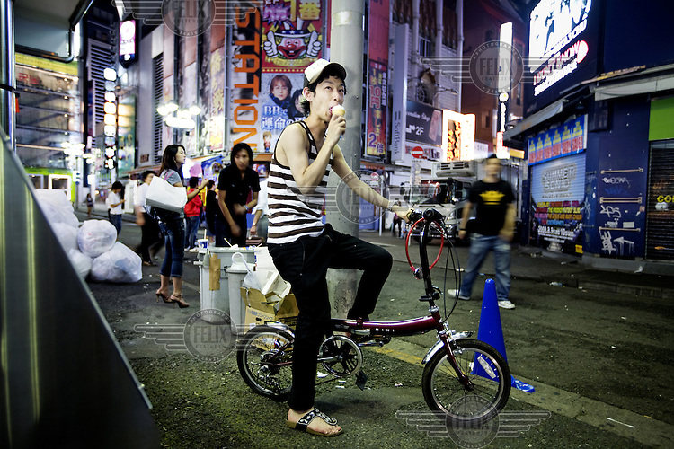 A young man, sits on a folding bicycle, eating ice cream.