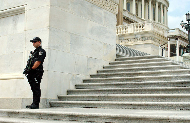 7/23/03.SECURITY--A U.S. Capitol Police officer carries an automatic weapon as he stands guard on the steps of the House side of the U.S. Capitol..CONGRESSIONAL QUARTERLY PHOTO BY SCOTT J. FERRELL