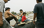 Wearing sandals with heels, a woman climbs aboard a makeshift raft to travel across the Suchiate River, the porous Mexico-Guatemala border, to Hidalgo, Mexico, on Tuesday, May 8, 2007, in Tecun Uman, Guatemala. Although many merchants usually ship goods on rafts to avoid an import tax, many Guatemalans become a part of the commericial traffic to avoid border police.