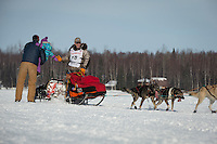 Jeff King gives a high-five to a spectator on Long Lake after leaving the re-start line of the Iditarod sled dog race in Willow, Alaska Sunday, March 3, 2013.