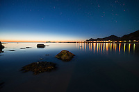 Village lights of Ramberg reflect over water, Flakstadøy, Lofoten Islands, Norway