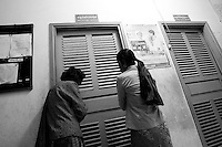 Health center Cambodia . Two grand mothers are trying to listen trough the door at Trapeng Andeuk health center. The granddaughter of one of them is giving birth in the delivery room. Trapeng Andeuk, Takeo province, Cambodia-2009