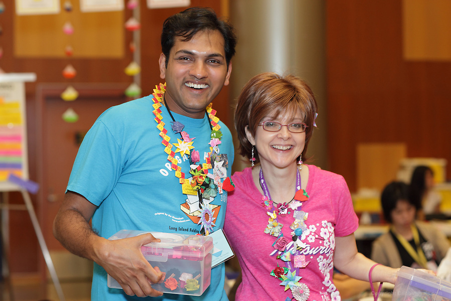 New York, NY, USA - June 23, 2012: Shri Iyer (left) and Tricia Tait display their collection of origami pins during the OrigamiUSA 2012 convention held at Fashion Institute of Technology in New York City. Attendees designed and made pins to bring to this event and swapped designs with others. The OrigamiUSA 2012 Convention held at Fashion Institute of Technology, New York, attracts members from the USA with visitors from Asia, the Americas, and Europe. Attendees exhibit their work and take part in classes, and an exhibition of big folding.