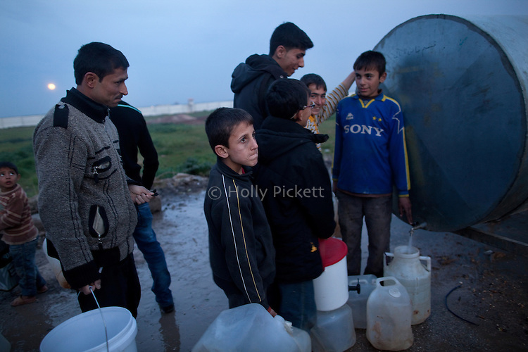 Boys and men collect drinking water from a tank at Azaz Camp, just inside the Syrian border with Turkey, Feb. 25, 2013. According to administrators, this camp holds roughly 9,000 to 10,000 internally displaced persons (IDP's). Two meals per day are provided by a Turkish humanitarian organization, and Qatar Red Crescent provided tents. There is very little electricity, and no running water. There is also a refugee camp on the Turkish side of the border, but it is full. The UN Refugee Agency has reported a sharp increase in refugees fleeing Syria for neighboring countries in the first months of 2013.