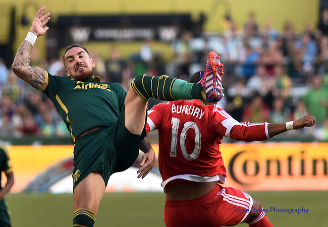 Jun 6, 2015; Portland, OR, USA; Portland Timbers defender Liam Ridgewell (24) and New England Revolution forward Teal Bunbury (10) go up for a ball during the first half of the game at Providence Park. Mandatory Credit: Steve Dykes-USA TODAY Sports