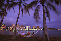 Couple relaxing in hammock between palm trees, with Waikiki and Diamond Head in background, just after sunset
