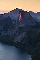 Last light illuminates vertical face of Segltind rising above Kjerkfjord, Moskenesøy, Lofoten Islands, Norway