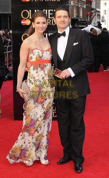 Summer Strallen & Tom Chambers.The Olivier Awards 2012, Royal Opera House, Covent Garden, London, England..April 15th, 2012.full length tuxedo black white strapless orange dress floral print .CAP/CAN.©Can Nguyen/Capital Pictures.