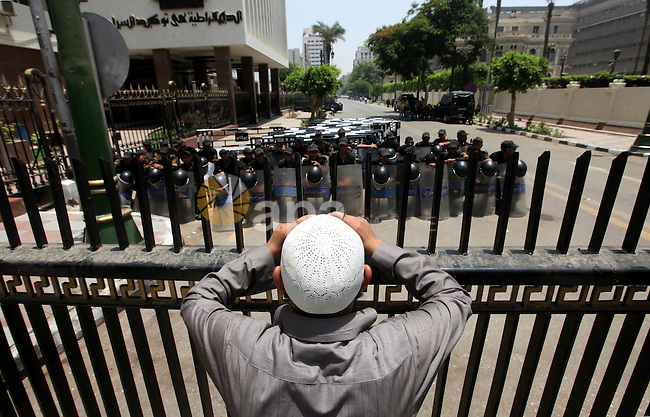 An Egyptian man stands in front of riot police blocking the access to the street of the parliament in Cairo, Egypt, 09 June 2012. A new constitutional document issued by the Supreme Council of the Armed Forces (SCAF), granted themselves all legislative powers. The ruling junta also issued a decree dissolving the Islamist-led parliament, following a court ruling which found the legislature to be unconstitutional. Photo by Majdi Fathi