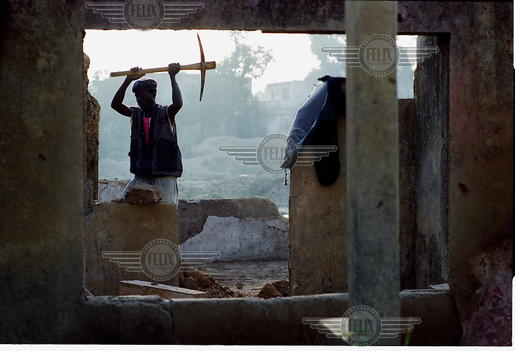 A worker removing damaged parts from a house with a pickaxe in the mining town of Koidu.
