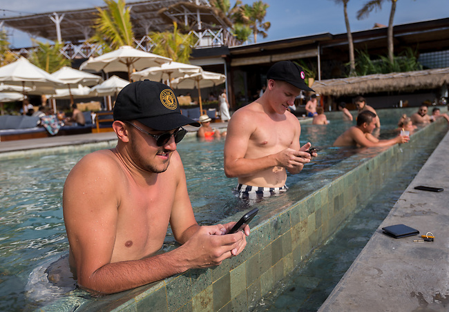 6 DECEMBER, 2019 BALI, INDONESIA:  Mitch Browne (right, 23) and Brendan Erceg (23) from Perth check their phones in the pool at The Lawn beach club in Canggu, Bali. There has been a levelling out of Australian tourist numbers to Bali in recent times and tastes are changing regarding what people want from their holiday. Millennials are being targeted by tourism authorities and they want to give them more boutique experiences than just beach and beer. Picture by Graham Crouch/The Australian