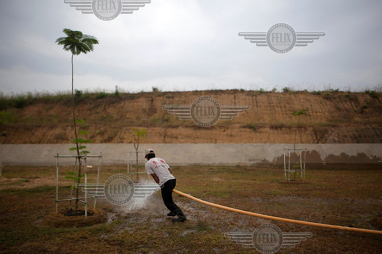 A worker waters a tree on the side of the road near parliament in Naypyitaw, the new capital of Burma (Myanmar) since November 2005.