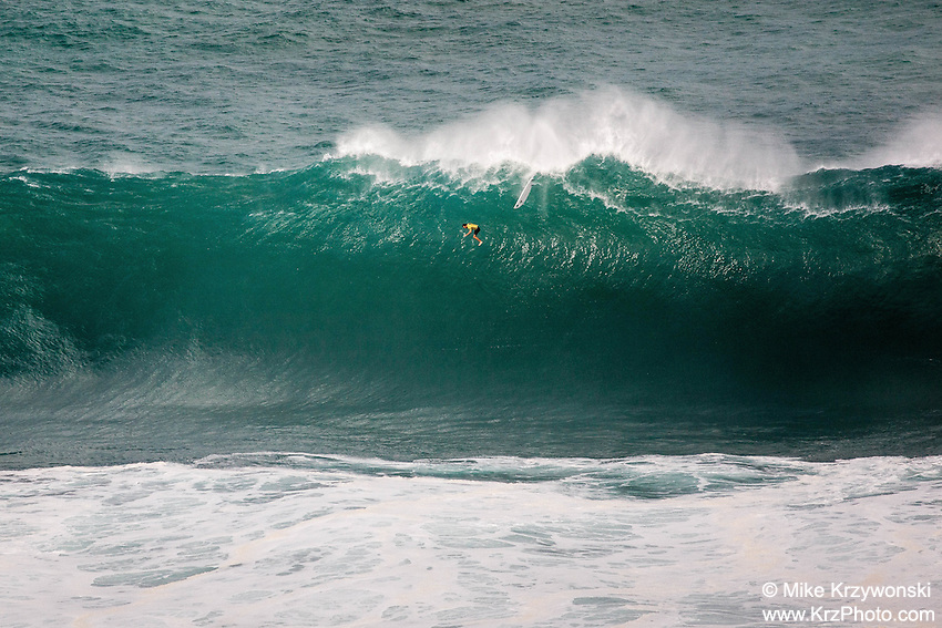 """Surfer Grant """"Twiggy"""" Baker free falling from the top of a wave at the 2016 Big Wave Eddie Aikau Contest, Waimea Bay, North Shore, Oahu"""