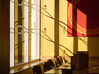 Strong, direct sunlight gives interesting shadows in a Pizza Hut restaurant.