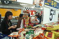 A Wal-Mart employee dressed in ethnic Chinese costume introduces shoppers to a variety of snacks, each priced at less than one U.S. dollar, at the Beijing Wal-Mart in Beijing, China on November 6, 2005.