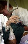 Gezondheidszorg > Verpleging:.Een geel verschrompelde hulploze oude hand is zichtbaar tijdens het voorzichtig verschonen van een bed door de verpleging..© Ton Borsboom.steekwoorden: editorial, Nederland, gezondheidszorg, healthcare, ziekenhuis, ziekenhuizen, hospitaal, kliniek, clinic, hospital, patient, zorg, medische sector, geneeskunde, detail, arbeidsomstandigheden, arbo, rug, bukken, zwaar, wia, werkdruk, ziektekosten, ziektekostenverzekering, zorgpolis, zorgverzekering, nood, detail, handen, staan, accuraat, arbeid, verpleging, verpleegster, verpleegkundige, hulpbehoevend, bejaard, hulpeloos.