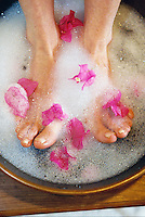 Closeup of bubble foot bath with pink bougainvillea flower petals