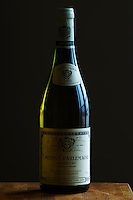 A bottle of Maison Louis Jadot Bourgogne Corton Charlemagne Grand Cru 2003 white burgundy wine standing on a wooden table top. Backlit backlight back light lit. gray grey background dark silhouette sidelit side light, Maison Louis Jadot, Beaune Côte Cote d Or Bourgogne Burgundy Burgundian France French Europe European