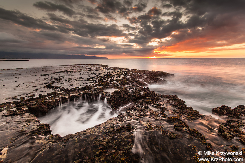 Water cascading off of a rocky shelf under a colorful sunset at Shark's Cove, North Shore, Oahu