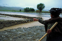 Farmer showing irrigation channel domaged from flooding
