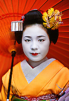 "Kyoto, Japan 2005.Komomo, a maiko with umbrella    This series of photos depicts an apprentice maiko, Komomo or ""little peach,"" in training with her onee-san ""older sister."" Yachiho-san is a fully trained geisha, or geiko as Kyoto's geisha are known. I was invited to enter the mysterious world of these artisans and access some private time with the girls as they prepared for their evening."