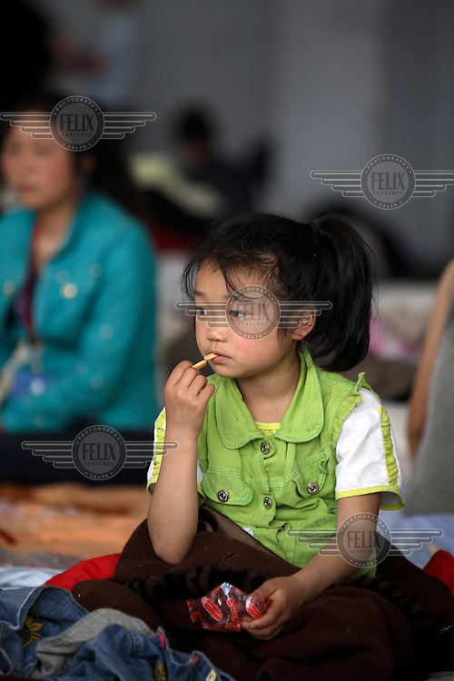 A child sits in a temporary shelter at the Jiuzhou Stadium in Mianyang. On the 12/05/2008 an earthquake measuring 8.0 on the Richter scale hit the province of Sichuan.