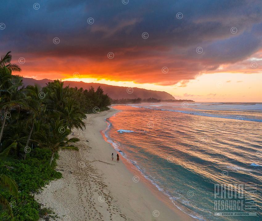 At sunset, two women look out to sea from Mokule'ia Beach near Crozier Drive, Waialua, North Shore, O'ahu.